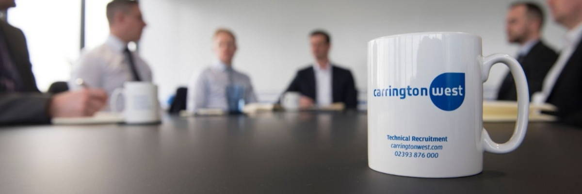 Carrington West branded mug with logo sitting on a boardroom table