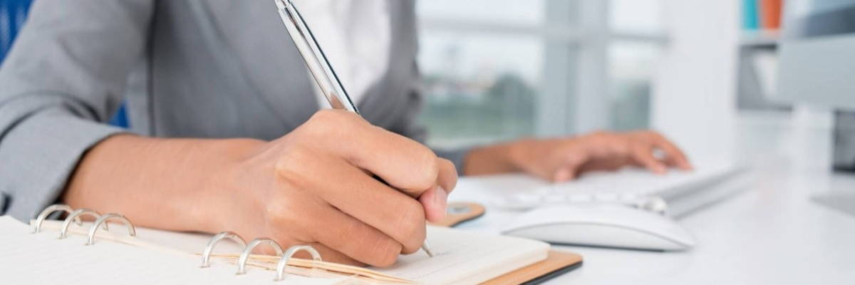 a person sitting at a desk writing